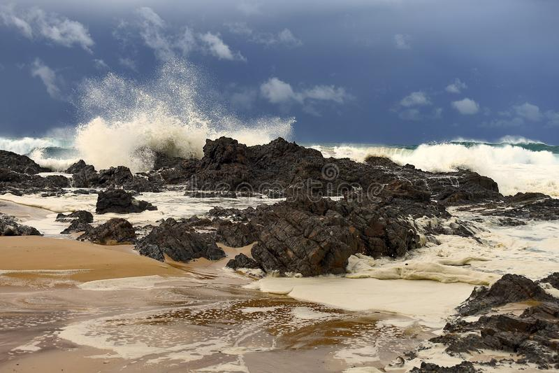 Reusachtige golven die over rotsen op oever verpletteren royalty-vrije stock foto's