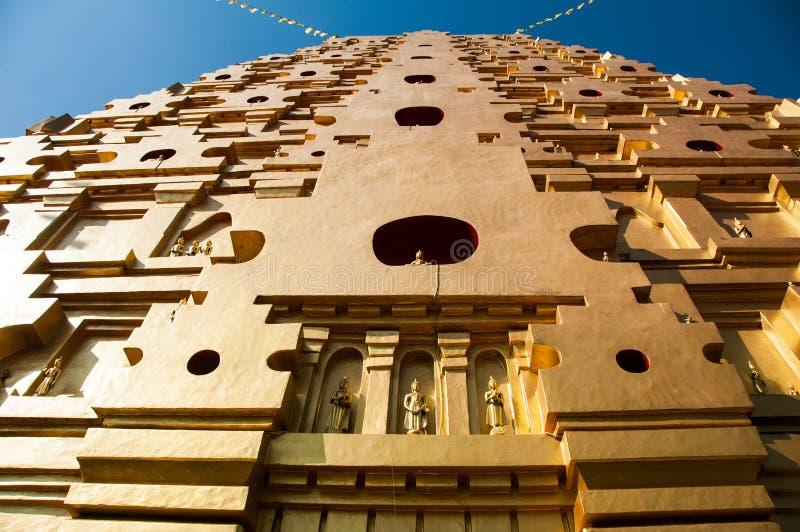 Reusachtige gouden pagode met vele standbeelden van Boedha stock foto