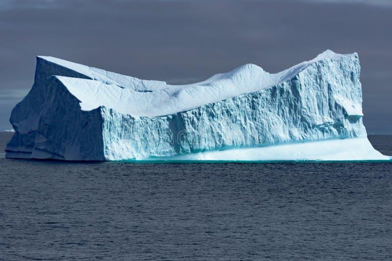 Reusachtige Ijsberg met steile helling glanzend turkoois op grijze dag in Groenland royalty-vrije stock afbeelding