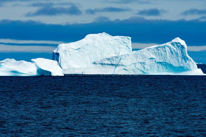 Reusachtige Ijsberg met steile helling glanzend turkoois op grijze dag in Groenland royalty-vrije stock foto