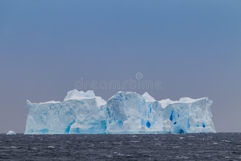 Reusachtige ijsberg van kust van Antarctica genoemd de Huwelijkscake stock foto's