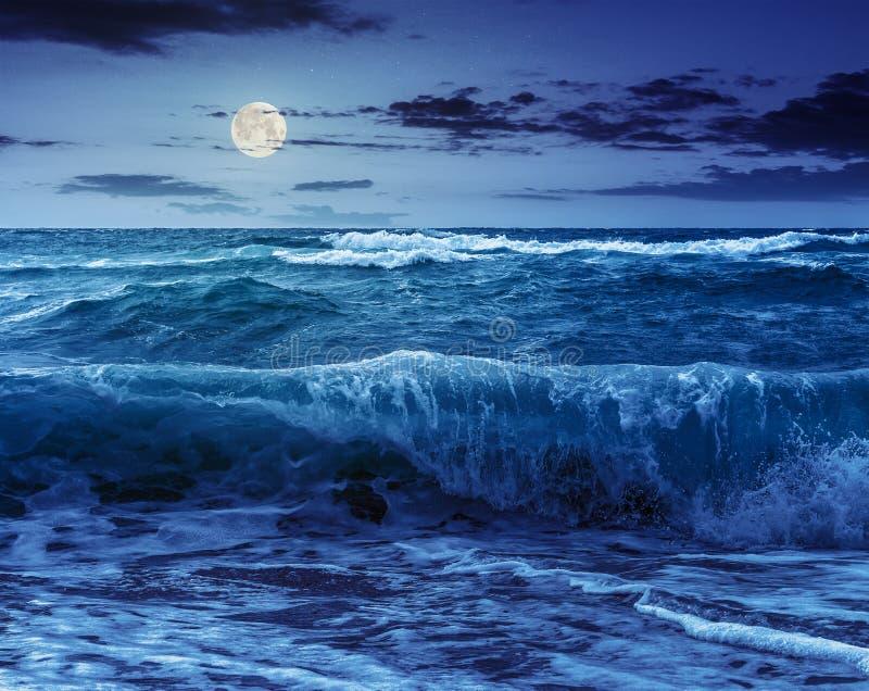 Reusachtige overzeese †golven ‹die †‹op zandig strand bij nacht lopen stock afbeeldingen