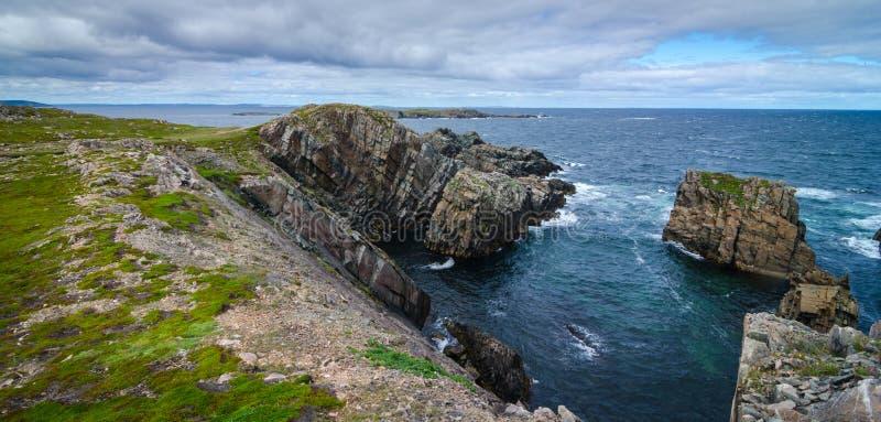 Reusachtige rotsen en keidagzomende aardlagen langs de kustlijn van Kaapbonavista in Newfoundland, Canada stock foto