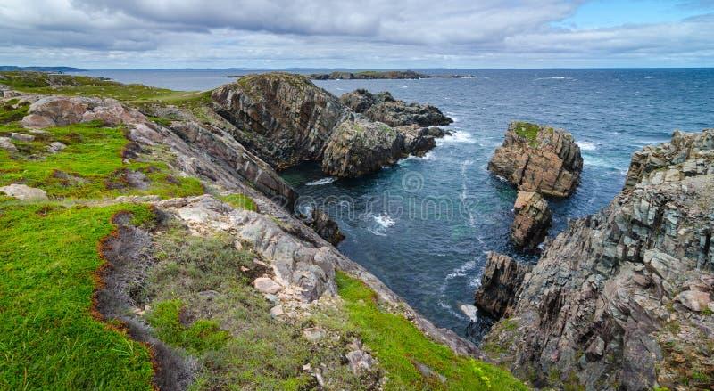 Reusachtige rotsen en keidagzomende aardlagen langs de kustlijn van Kaapbonavista in Newfoundland, Canada stock foto's