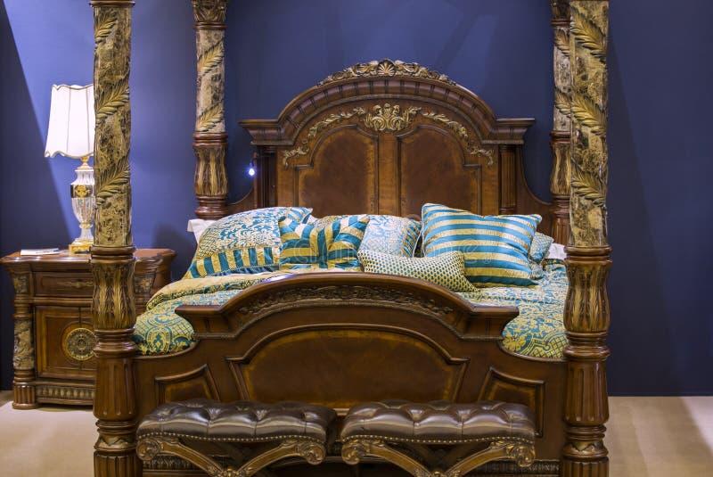 Reusachtige slaapkamer in houten stijl, gesneden elegant houten bed met kolommen en stoles, bedlijsten en ander meubilair in de s royalty-vrije stock afbeelding