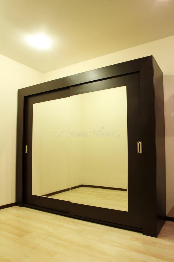 Reusachtige spiegelgarderobe in beige toonruimte royalty-vrije stock afbeelding