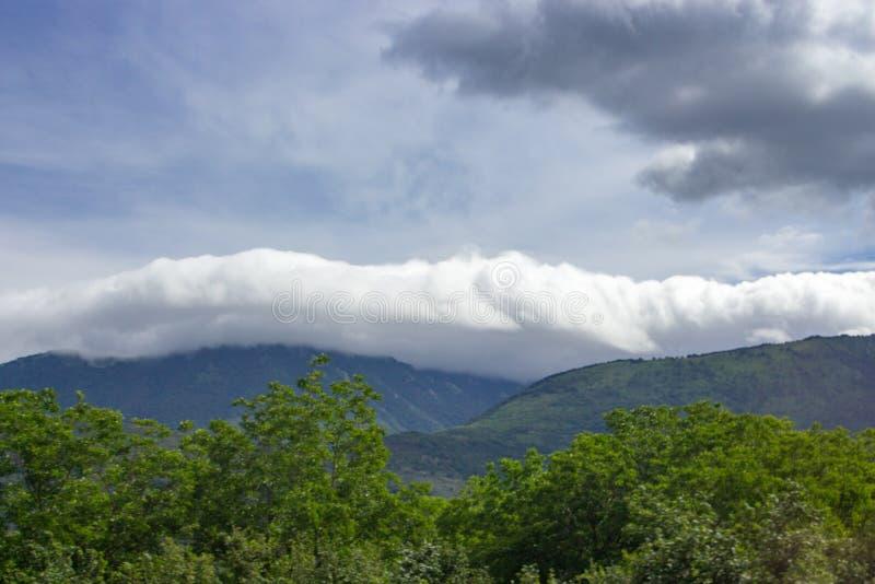 Reusachtige wolken over bergen met groen bomenvoorhoofd Aard en elementenconcept Onweersachtergrond royalty-vrije stock foto