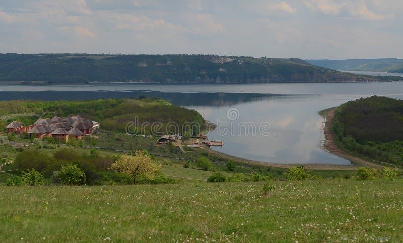 Reusachtige zuivere steenklippen op de achtergrond van een rivier Dniester en een blauwe hemel met wolken royalty-vrije stock afbeelding