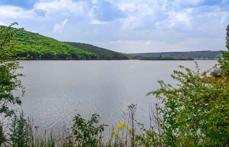 Reusachtige zuivere steenklippen op de achtergrond van een rivier Dniester en een blauwe hemel met wolken stock foto's