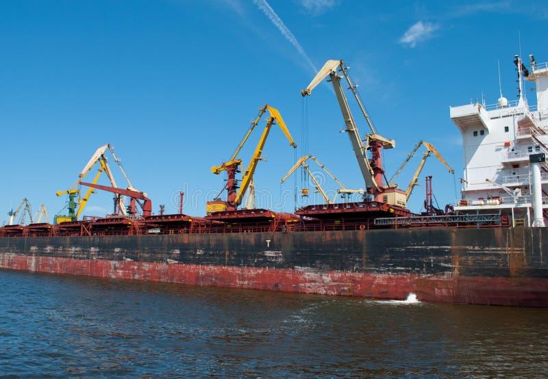 Reuze havenkranen en een vrachtschip royalty-vrije stock afbeelding