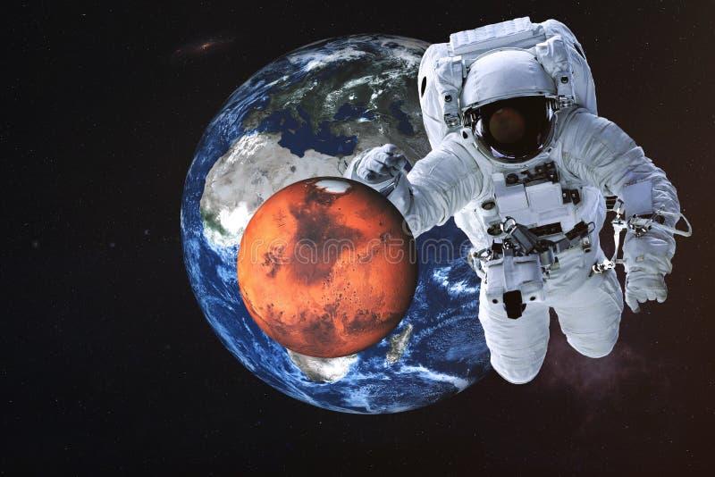 Reuzeastronaut dichtbij de planeten van Mars en van de Aarde stock foto