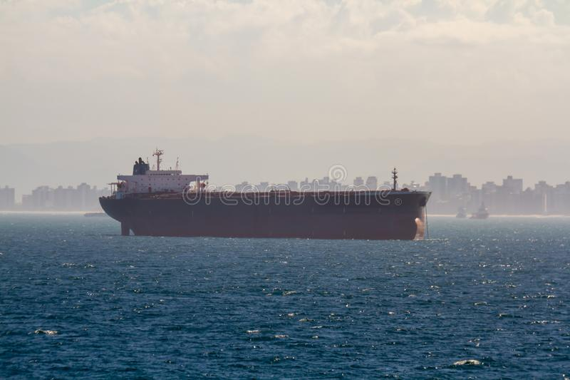 Reuzebulkladingschip ver weg bij achorage met mooie stad op achtergrond royalty-vrije stock afbeeldingen