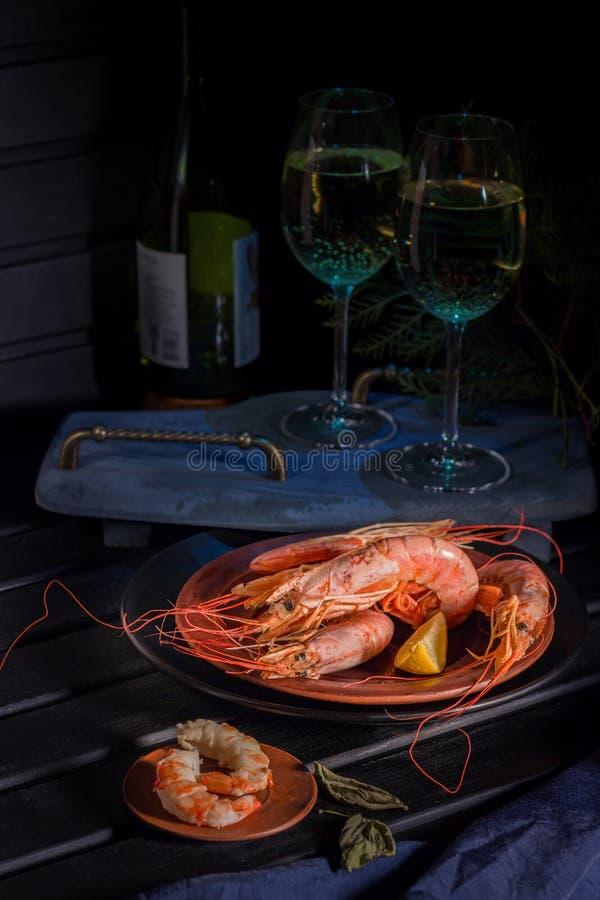 Reuzegarnalen, citroen, twee glazen witte wijn Heldere foto op een zwarte achtergrond royalty-vrije stock foto