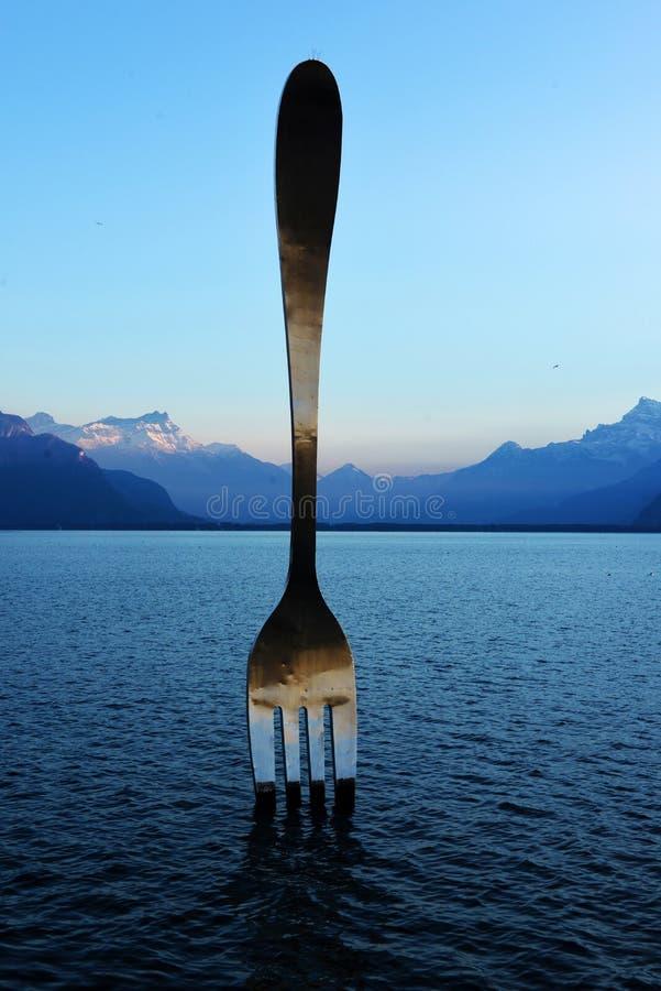Reuzestaalvork in water van het meer Vevey van Genève stock foto