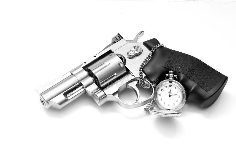 Revólver e um relógio de bolso fotos de stock royalty free
