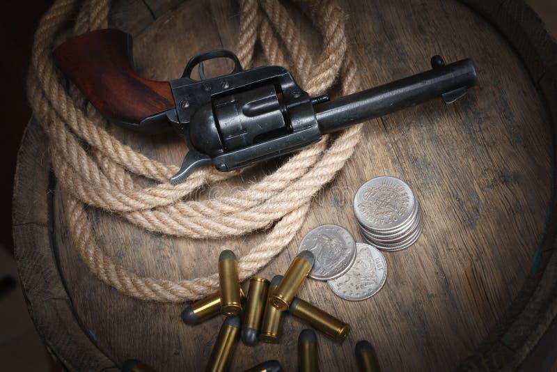 Revólver ocidental velho com cartuchos e dólar de prata imagem de stock royalty free