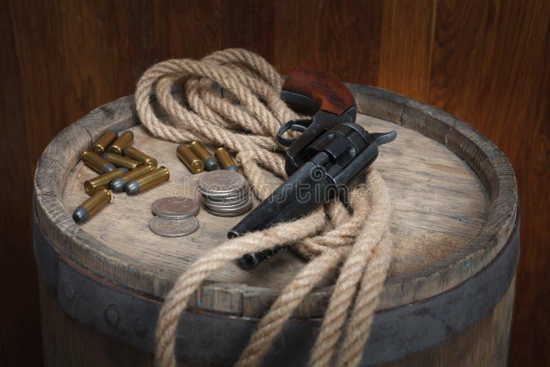 Revólver ocidental velho com cartuchos e dólar de prata fotografia de stock