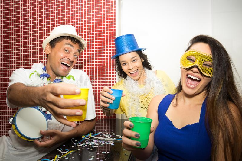 Revelers making funny photo. Group of friends celebrate the Carnaval in Brazil.. Revelers are laughing and having fun. They are looking and pointing at the stock photos