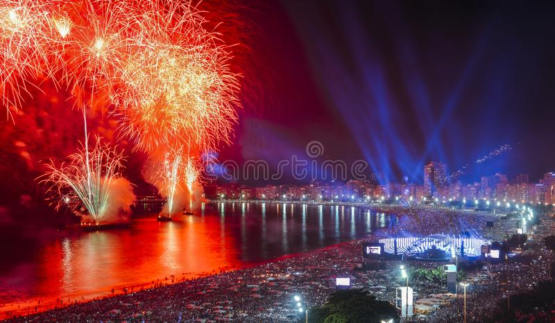 Iconic and breath-taking fireworks display on Copacabana Beach, Rio de Janeiro, Brazil. Revellers, both locals and tourist, enjoy the breath-taking New Years stock photography