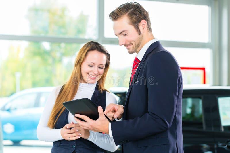 Revendeur, client féminin et automobile au concessionnaire automobile photo stock