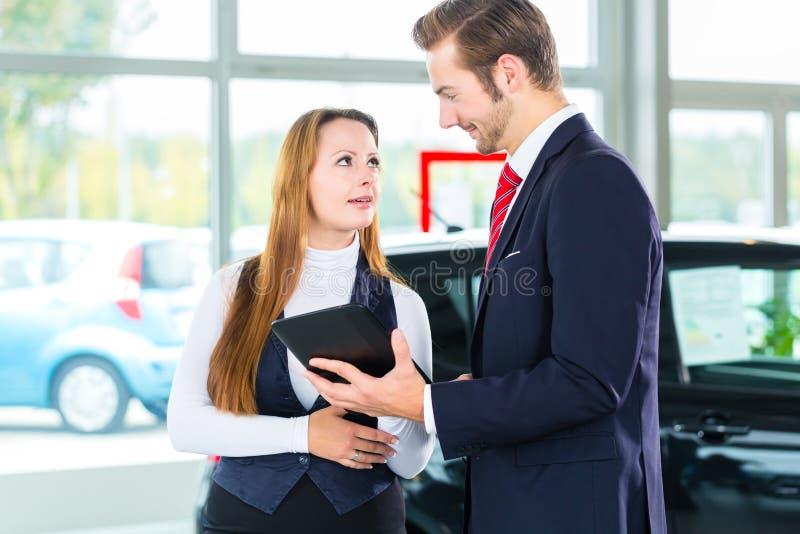 Revendeur, client féminin et automobile au concessionnaire automobile image stock