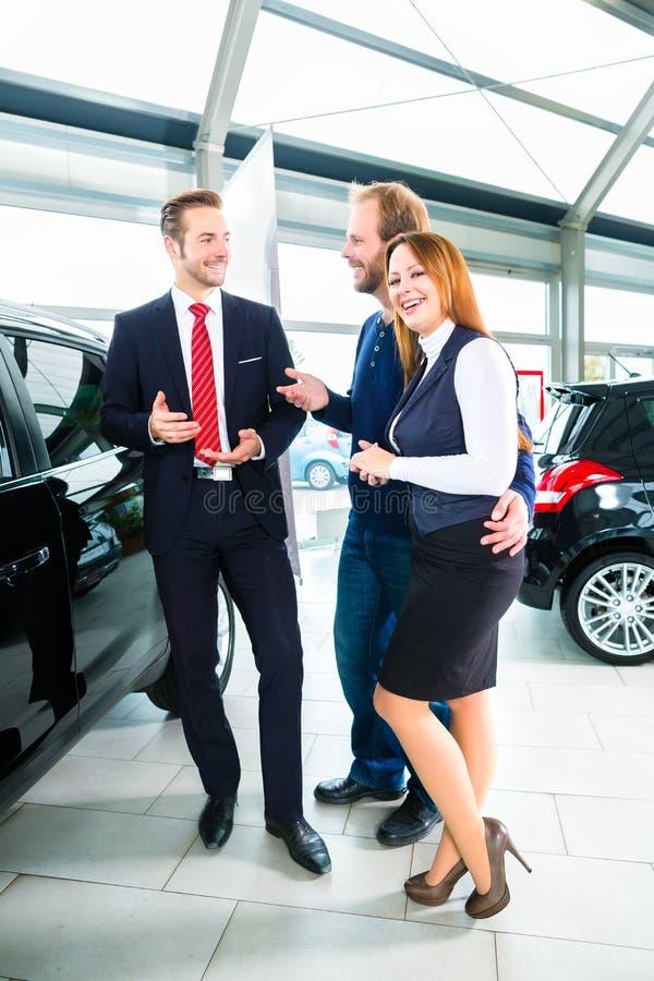 Revendeur, clients et automobile au concessionnaire automobile photographie stock libre de droits