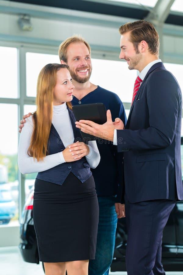 Revendeur, clients et automobile au concessionnaire automobile images libres de droits