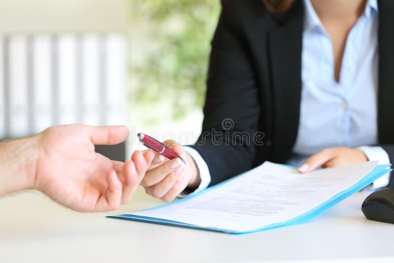 Revendeur donnant un stylo à un client pour signer un contrat photo stock