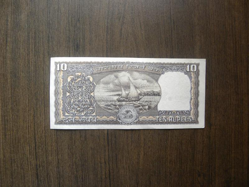 Old ten rupees note. Reverse of black color old 10 rupees India banknote with boat in the ocean portrait kept on wooden table stock images