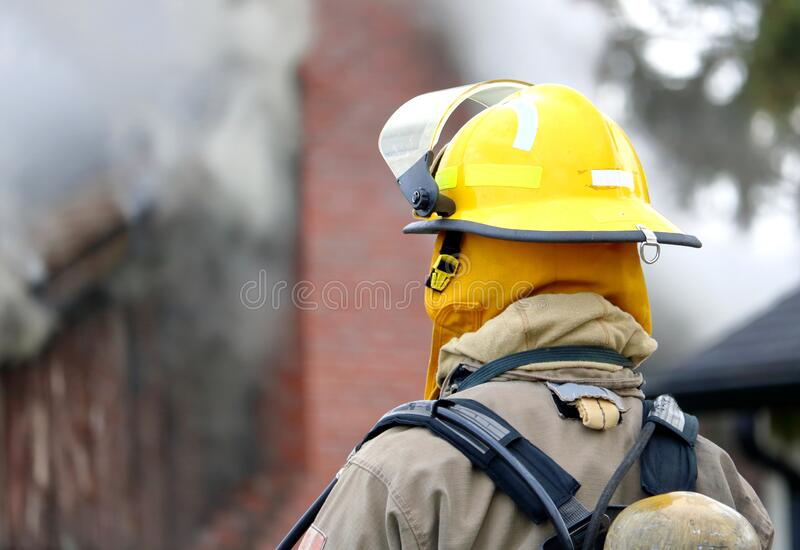 Firefighter Watching House Fire. Reverse close view of a firefighter in full gear with a smoking building in the background stock photos