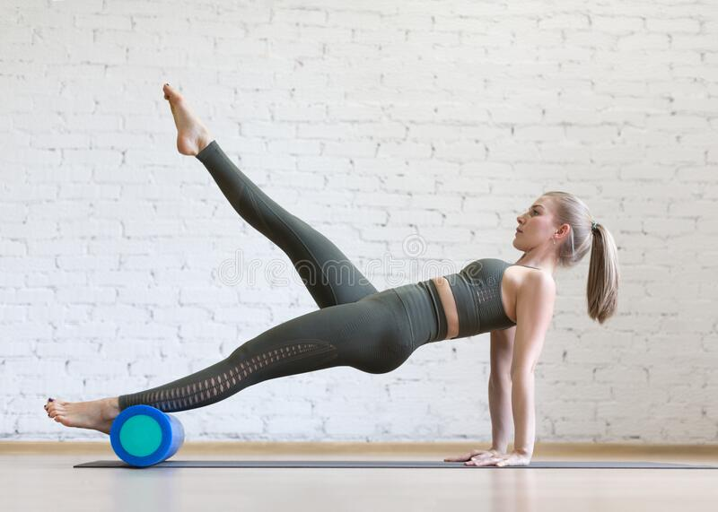 Reverse plank exercise with foam roller. Young fit woman does pilates in loft fitness studio, indoor. stock images