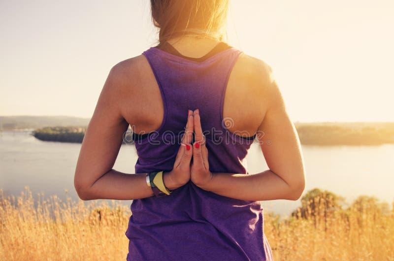 Reverse prayer yoga pose, young woman royalty free stock image
