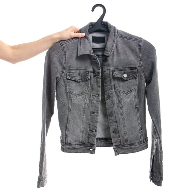 Revestimento cinzento das calças de brim em um gancho à disposição foto de stock royalty free