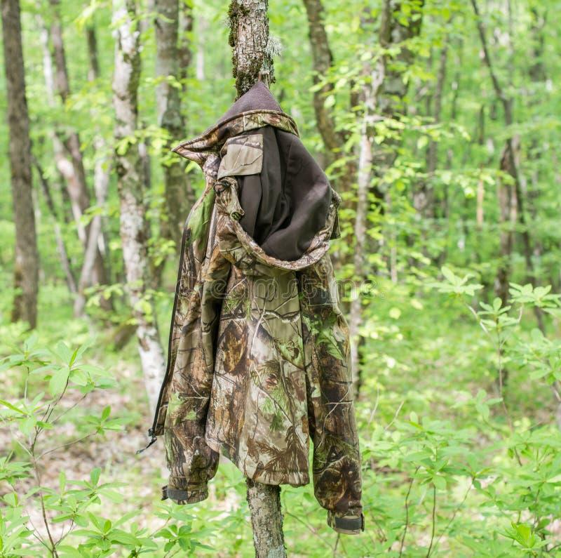 Revestimento da camuflagem do ` s do caçador que pendura na árvore na madeira fotos de stock