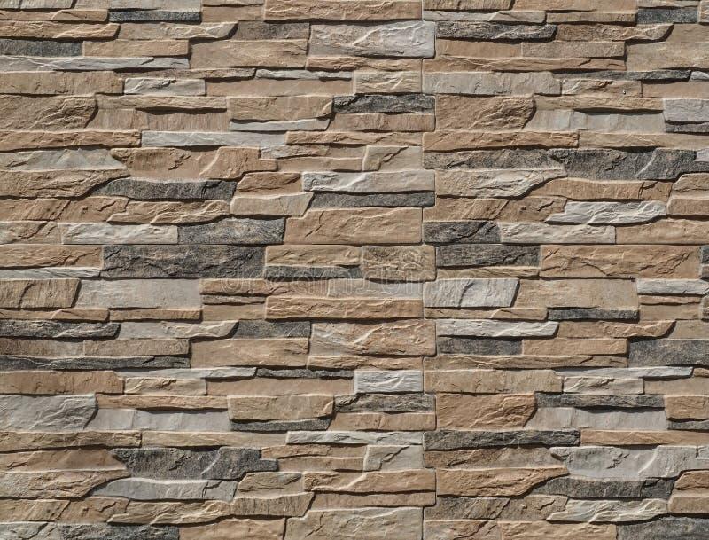 Revestimento da parede de pedra feito de rochas artificiais das listras As cores são preto, marrom e cinza imagens de stock