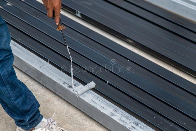 Revestimento de pintura do metal do trabalhador para proteger da oxidação na estrutura do metal imagem de stock