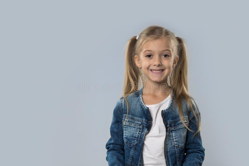 Revestimento de sorriso feliz das calças de brim do desgaste da menina bonita isolado foto de stock