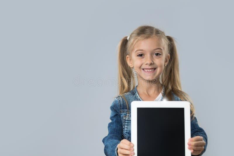 Revestimento de sorriso feliz das calças de brim do desgaste da tela vazia bonita do tablet pc da posse da menina isolado foto de stock