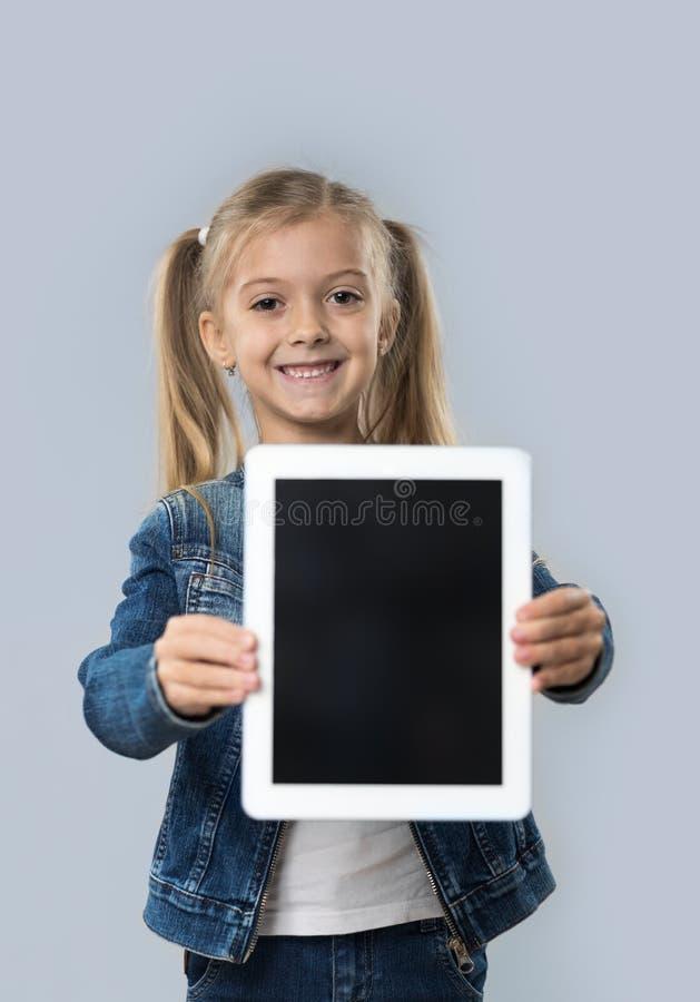 Revestimento de sorriso feliz das calças de brim do desgaste da tela vazia bonita do tablet pc da posse da menina isolado fotografia de stock
