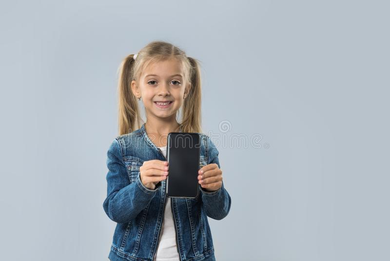 Revestimento de sorriso feliz das calças de brim do desgaste da tela vazia esperta bonita do telefone da pilha da posse da menina fotos de stock