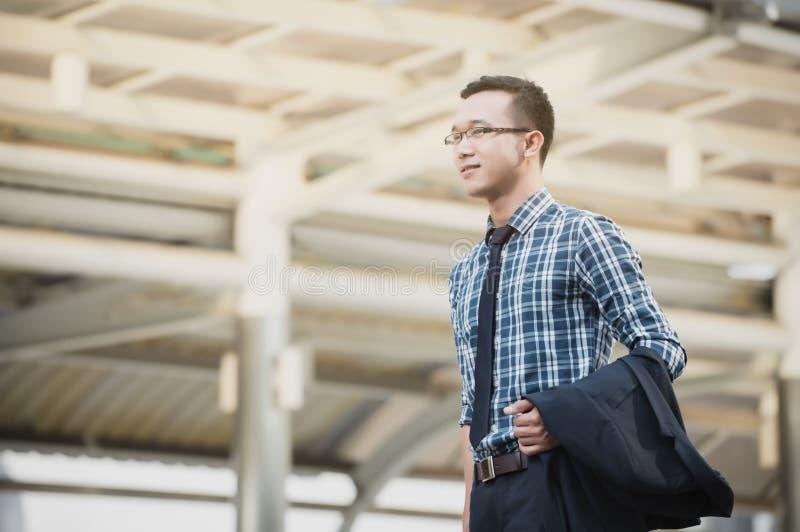 Revestimento ereto do homem de negócios novo de Ásia o lado que olha para fotografia de stock