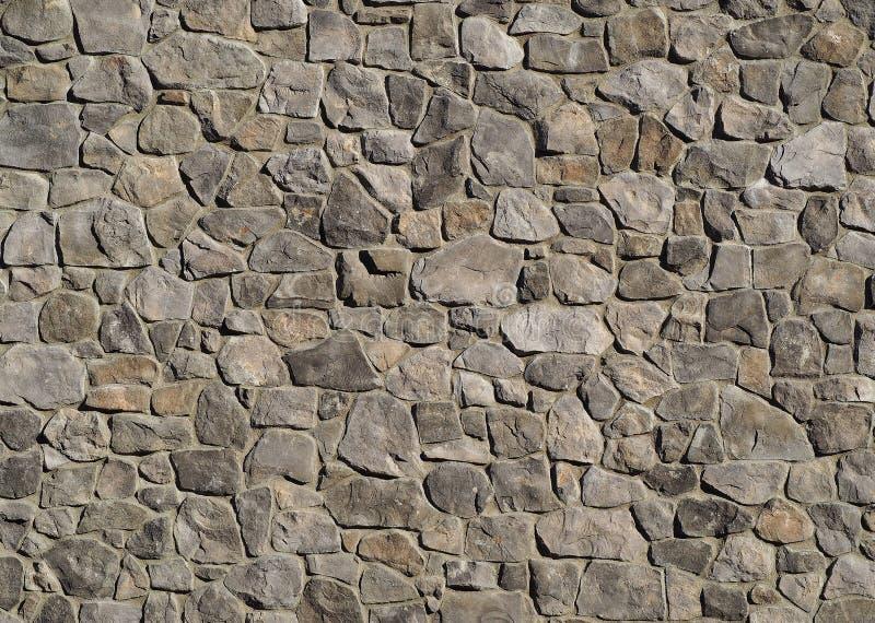 Revestimento maciço da parede exterior feito de pedras naturais cinzentas com tamanhos e formas diferentes fotografia de stock