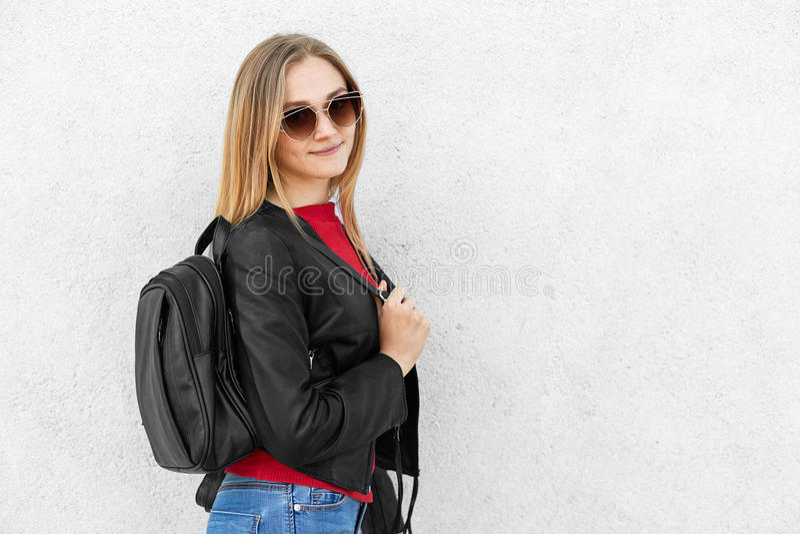 Revestimento preto de couro vestindo fêmea novo, óculos de sol na moda e calças de brim tendo a mochila que levanta contra o muro imagens de stock