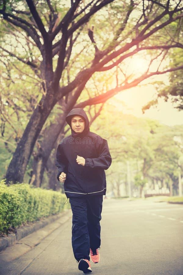 Revestimento vestindo da capa do homem novo que corre na rua urbana imagens de stock royalty free