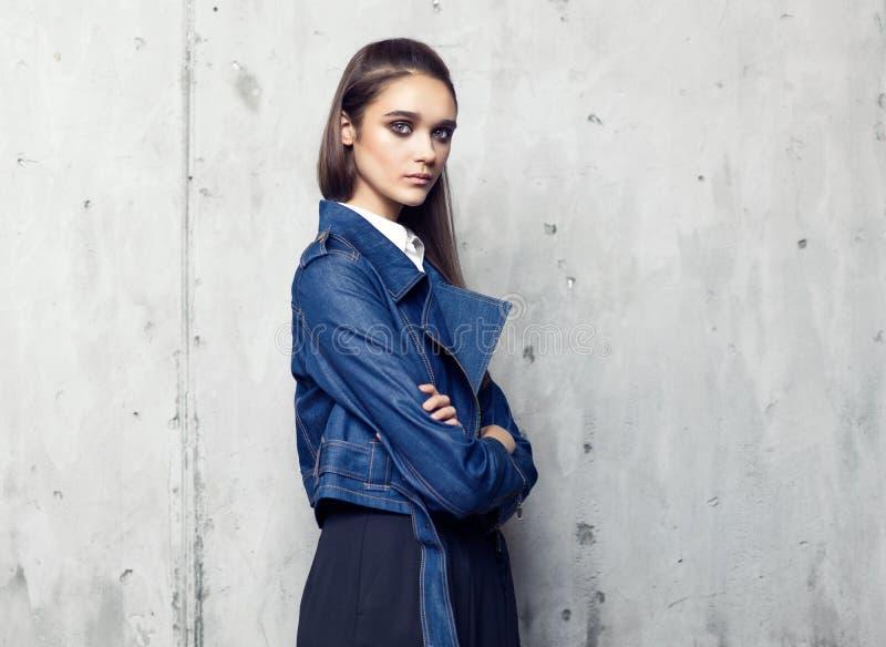 Revestimento vestindo da sarja de Nimes do modelo de forma e saia preta longa que levantam no estúdio fotos de stock
