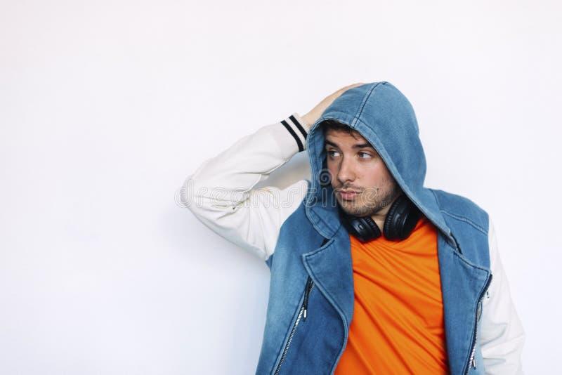 Revestimento vestindo das cal?as de brim do homem consider?vel novo com capa sobre e fones de ouvido em sua posi??o do pesco?o co fotografia de stock