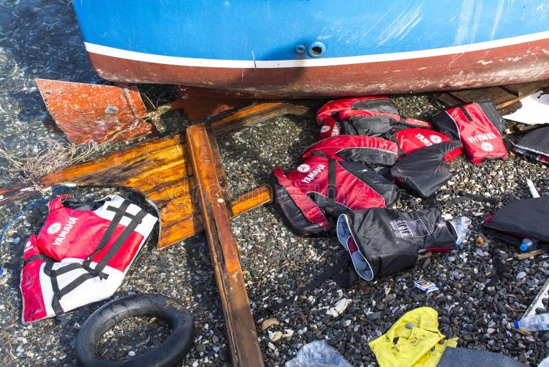 Revestimentos de vida rejeitados em uma praia Os refugiados vêm de Turquia em um barco inflável fotos de stock
