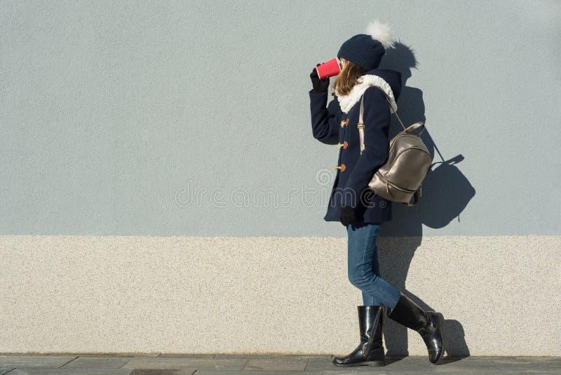 Revestimentos do estudante fêmea do retrato do inverno e chapéu vestindo exteriores da malha com trouxa, com o copo da bebida que imagens de stock