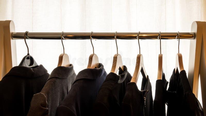 Revestimentos escuros do terno em ganchos na frente de um fundo branco imagem de stock