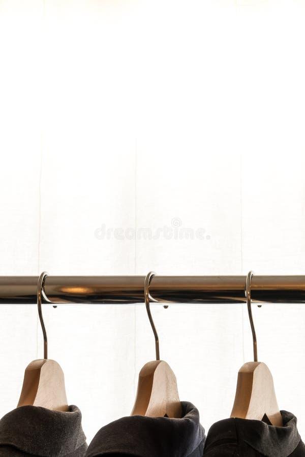 Revestimentos escuros do terno em ganchos na frente de um fundo branco imagem de stock royalty free